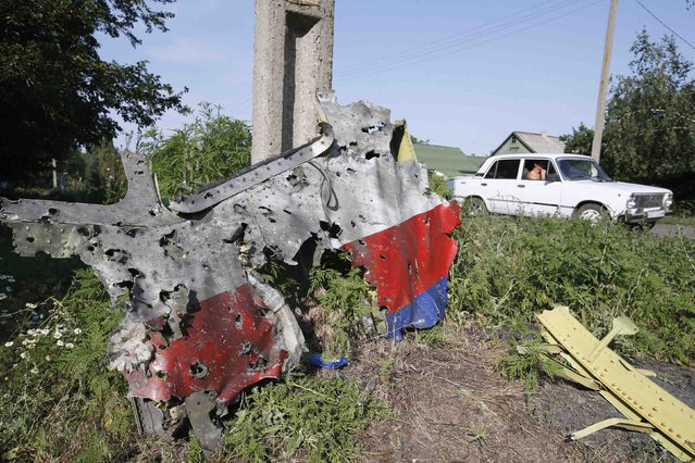 A piece of the wreckage is seen at a crash site of the Malaysia Airlines Flight MH17 in the village of Petropavlivka (Petropavlovka), Donetsk region July 24, 2014. (Photo by Maxim Zmeyev/Reuters)