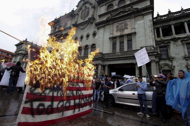 Demonstrators burn a U.S. flag during a protest to demand the resignation of Guatemala's President Otto Perez Molina, in Guatemala City, August 15, 2015. (Photo by Josue Decavele/Reuters)