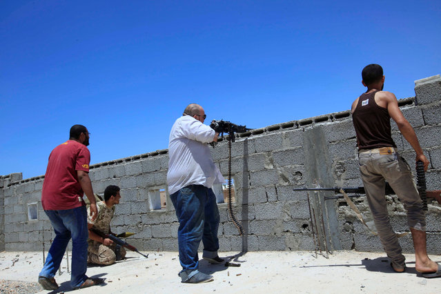 Fighters from forces aligned with Libya's new unity government fire a weapon from atop a house on an Islamic State position in the Seven hundred neighbourhood in Sirte June 29, 2016. (Photo by Ismail Zitouny/Reuters)
