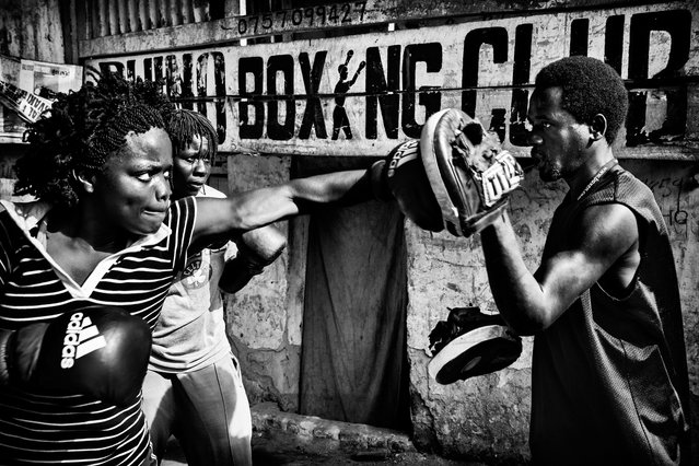 July 23, 2013 – Kampala, Uganda. Helene and Diana train daily more than 2.5 hours by Innocent Kapalata, a passionate and ambitious former boxer. Amidst the shanty homes a group of ambitious fighters are trying to reach for a better life. (Photo by Peter Bauza/ZUMA Press/VISUAL Press)