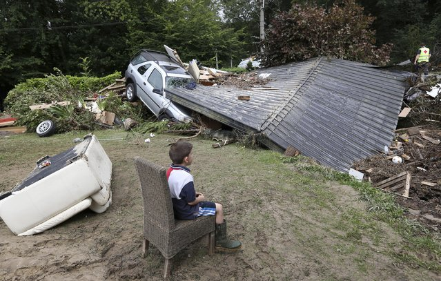 A boy sits near a car stuck under a roof, which collapsed after heavy rains and floods hit the town of Ittre July 30, 2014. (Photo by Francois Lenoir/Reuters)