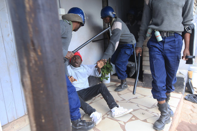 Armed Zimbabwean police detain an alleged rioter in Harare, Monday, July, 4, 2016, as police in the capital fired tear gas and water cannons to quell rioting by taxi and mini bus drivers. (Photo by Tsvangirayi Mukwazhi/AP Photo)