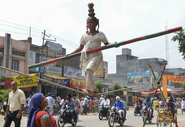 This August 28, 2017 photo shows eight-year-old Indian girl Bharti performing a balancing act on a rope during a street show in Batala, India. Travelling Indian performers, who earn a meagre income from putting on shows on the streets, often scout areas to gather a large street audience who then give money on a collection plate at the end of the show. (Photo by Narinder Nanu/AFP Photo)