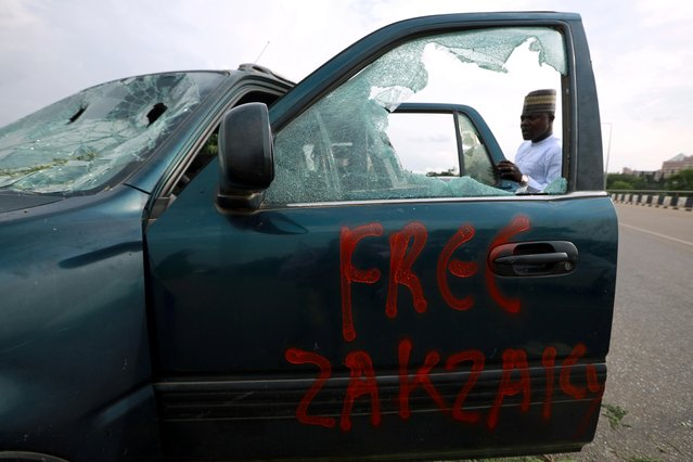 """Free Zakzaky"" (imprisoned leader of the Islamic Movement of Nigeria (IMN) Ibrahim Zakzaky) reads on a damaged car outside the National Assembly in Abuja, Nigeria on July 9, 2019. Supporters of an imprisoned Shiite cleric clashed on July 8, 2019 with security forces around Nigeria's parliament building, leaving a number of wounded, including two police, the authorities and witneses said. Two officers were shot in the legs and six others hit with clubs and stones as members of the Islamic Movement of Nigeria (IMN) tried to ""force their way into the National Assembly"", police said. (Photo by Afolabi Sotunde/Reuters)"