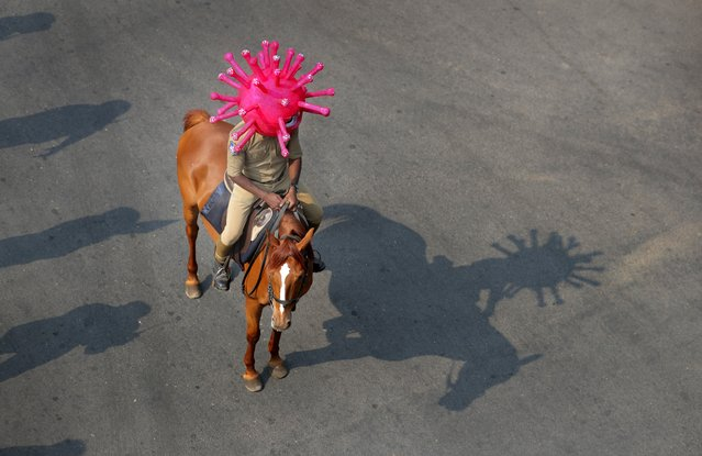 An Indian policeman wearing a virus themed helmet rides on a horse during an awareness rally aimed at preventing the spread of new coronavirus in Hyderabad, India, Thursday, April 2, 2020. (Photo by Mahesh Kumar A./AP Photo)