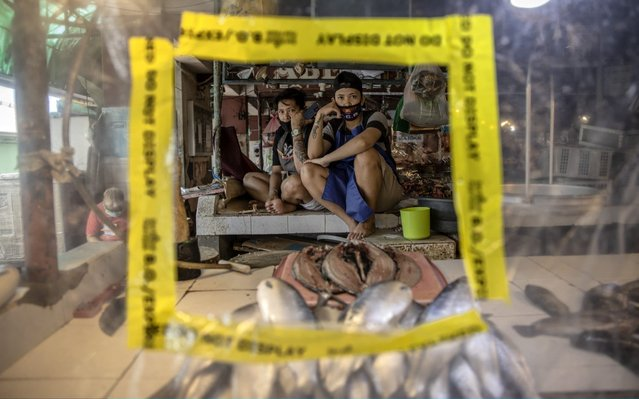 Vendors rest in their stall covered in plastic to enforce social distancing on March 30, 2020 in Las Pinas, Metro Manila, Philippines. The Philippine government has sealed off Luzon, the country's largest and most populous island, to prevent the spread of COVID-19. Land, sea, and air travel has been suspended, while government work, schools, businesses, and public transportation have been ordered shut in a bid to keep some 55 million people at home. The Philippines' Department of Health has so far confirmed 1418 cases of the new coronavirus in the country, with at least 71 recorded fatalities. (Photo by Ezra Acayan/Getty Images)