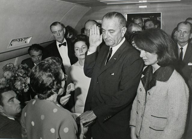 U.S. Vice President Lyndon Baines Johnson (C) takes the presidential oath of office from Judge Sarah T. Hughes (2nd from L) as President John F. Kennedy's widow first lady Jacqueline Bouvier Kennedy (2nd from R) stands at his side aboard Air Force One at Love Field in Dallas, Texas just two hours after Kennedy was shot in this November 22, 1963 photo by White House photographer Cecil Stoughton provided by the John F. Kennedy Presidential Library in Boston. (Photo by Cecil Stoughton/Reuters/JFK Library/The White House)
