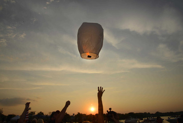A sky lantern is released during a vigil at Lakefront Park to honor Lt. Charles Joseph Gliniewicz, Wednesday, September 2, 2015, in Fox Lake, Ill. Gliniewicz was shot and killed Tuesday while pursuing a group of suspicious men. Authorities broadened the hunt Wednesday for the suspects wanted in the fatal shooting. (Photo by John Starks/Daily Herald via AP Photo)