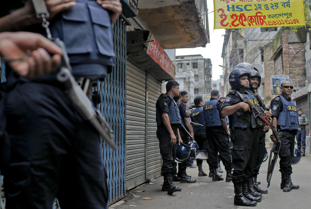 Bangladeshi security men stand guard on a street close to a five-story building that was raided by police in Dhaka, Bangladesh, Tuesday, July 26, 2016. (Photo by AP Photo)