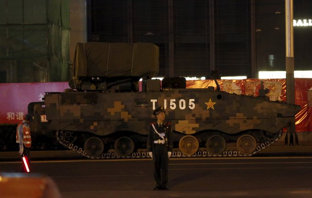 A paramilitary policeman stands guard in front of an armored vehicle which is parked for the upcoming military parade to mark the 70th Anniversary of the end of World War Two, in Beijing, China, September 2, 2015. (Photo by Kim Kyung-Hoon/Reuters)