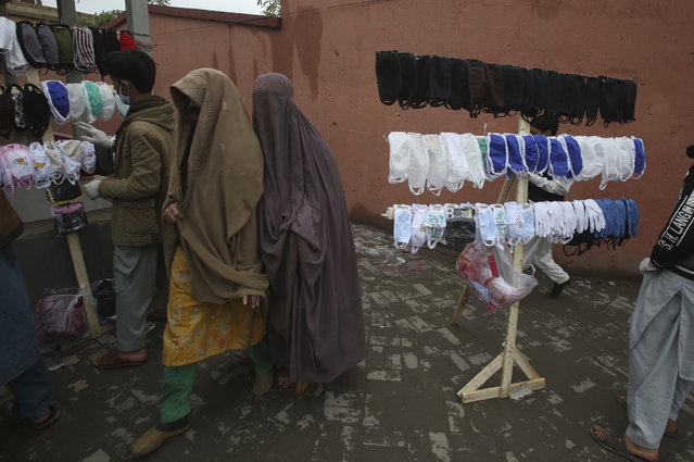Pakistani women walk past vendors selling face masks to prevent the spread of the coronavirus, in Peshawar, Pakistan, Tuesday, March 24, 2020. Pakistani authorities said they'd shut down train operations across the country from Wednesday until March 31 in an effort to contain the spread of the virus. (Photo by Muhammad Sajjad/AP Photo)