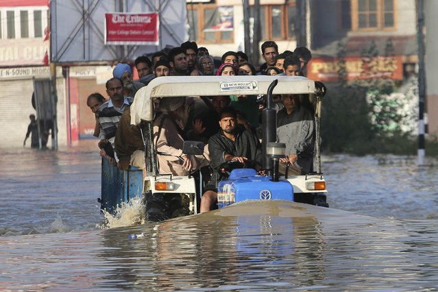 Kashmiri residents are evacuated in a tractor from their flooded neighborhood in Srinagar, India, Sunday, September 7, 2014. (Photo by Dar Yasin/AP Photo)