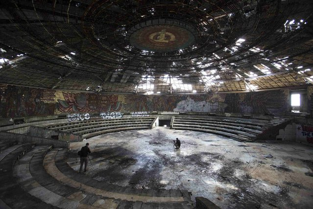 Photographers take pictures inside the crumbling main hall of the Memorial House of the Bulgarian Communist Party on mount Buzludzha September 12, 2014. (Photo by Stoyan Nenov/Reuters)
