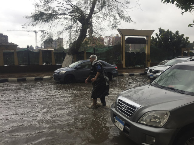 A man wears makeshift rain gear as he navigates a flooded road after heavy rains in the Zamalek district of Cairo, Egypt, Thursday, March 12, 2020. Thunderstorms packing heavy rains and lightning caused widespread flooding in Egypt on Thursday, killing several people and causing authorities to shut down schools and an airport, officials said. (Photo by Maya Alleruzzo/AP Photo)