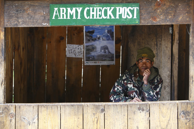 A Nepalese army personnel sits inside a check post as he waits to check permits for trekkers passing by, in Solukhumbu District April 26, 2014. (Photo by Navesh Chitrakar/Reuters)