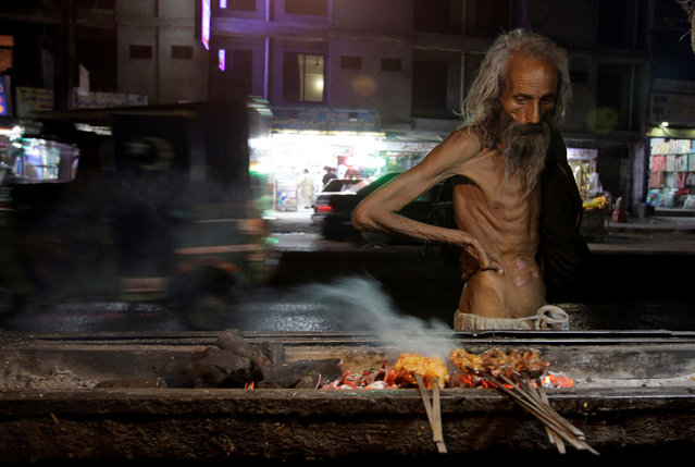 A man looks at kebabs cooking on the street side in Rawalpindi, Pakistan October 2, 2017. (Photo by Caren Firouz/Reuters)