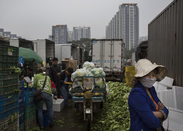 A Chinese vegetable vendor wears a mask at a local market on September 26, 2014 in Beijing, China.. (Photo by Kevin Frayer/Getty Images)