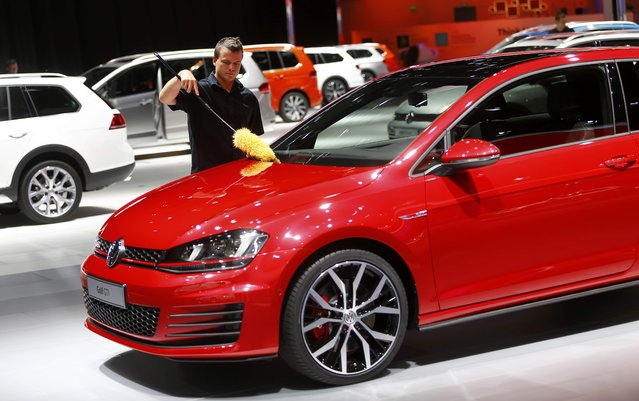 An employee dusts off a Volkswagen Golf GTI car during the media day at the Frankfurt Motor Show (IAA) in Frankfurt, Germany, September 14, 2015. (Photo by Kai Pfaffenbach/Reuters)
