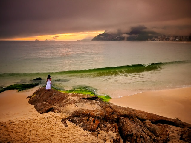 """Ipanema Beach, Rio de Janeiro. """"A rainy day in Rio and nobody goes out! Of course, I love rainy-day light because I know special things can happen. I went to Ipanema with my assistant and she went out on to Arpoador rock. The rain let up for a bit, and the magic light gave us this colour palette"""". (Photo by David Alan Harvey/The Guardian)"""