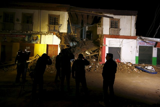 Members of the media gather in front of a damaged building after an earthquake hit areas of central Chile, in Illapel town, north of Santiago, Chile, September 17, 2015. More than a million people were forced from their homes after a magnitude 8.3 earthquake struck in the Pacific Ocean off Chile, slamming powerful waves into coastal towns and killing at least five people. (Photo by Ivan Alvarado/Reuters)