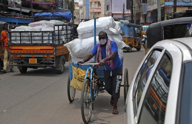 An Indian cycle rickshaw puller wearing face mask transports a load in Hyderabad, India, Thursday, June 25, 2020. India is the fourth hardest-hit country by the pandemic in the world after the U.S., Russia and Brazil. (Photo by Mahesh Kumar A./AP Photo)