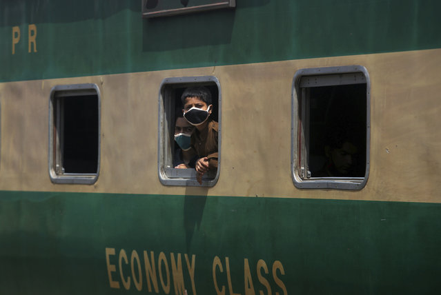 Boys wearing protective masks to help curb the spread of the coronavirus, look out the window of a train at a railway station, in Karachi, Pakistan, Saturday, January 6, 2020. (Photo by Fareed Khan/AP Photo)