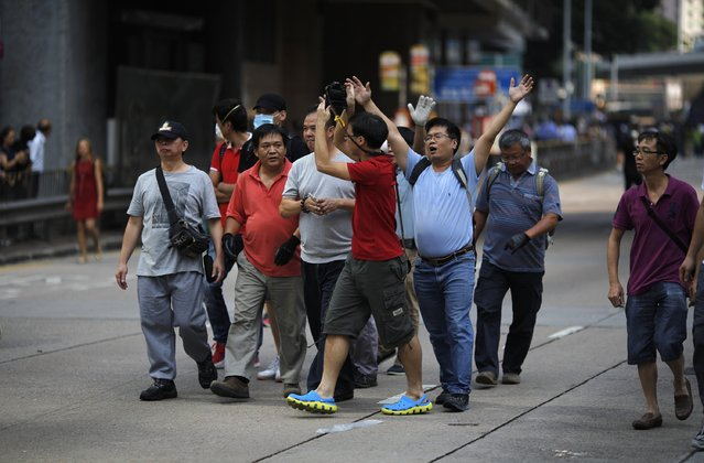 Anti-Occupy protesters block a photographer taking pictures of fellow anti-Occupy demonstrators removing barricades and tents (obscured) at the main protest site in Admiralty in Hong Kong October 13, 2014. (Photo by Carlos Barria/Reuters)