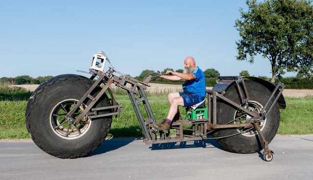 Frank Dose rides his huge bicycle in Rade, Germany, 27 August 2016. Dose aims to achieve the Guinness world record for the heaviest ridable bicycle. The bike currently weighs 940 kilograms, but its creator wants to increase the weight to 1.2 metric tons. (Photo by Markus Scholz/APA)
