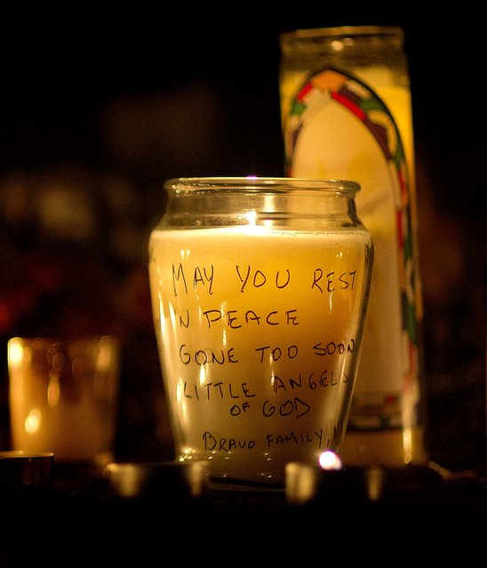 A message is seen on a candle outside St. Rose of Lima Roman Catholic Church. (Photo by David Goldman/Associated Press)
