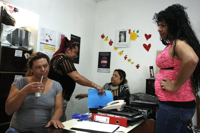 """In this November 13, 2017 photo, transgender Mariana Sepulveda sips """"terere"""", a cold, herbal tea, as she works with Panambi board members Marcela Valdez, behind left, Yren Rotelam center, and Tamara Amarilla in Asuncion, Paraguay. """"Raising a family, having a partner, adopting children seems out of reach because there are no legal conditions for us in Paraguay"""", said Sepulveda, 32, who now works for the advocacy group. (Photo by Jorge Saenz/AP Photo)"""