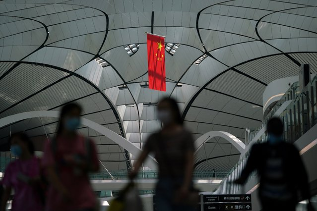 People wearing face masks following the coronavirus disease (COVID-19) outbreak walk under a Chinese flag at Beijing Daxing International Airport in Beijing, China on July 24, 2020. (Photo by Thomas Suen/Reuters)