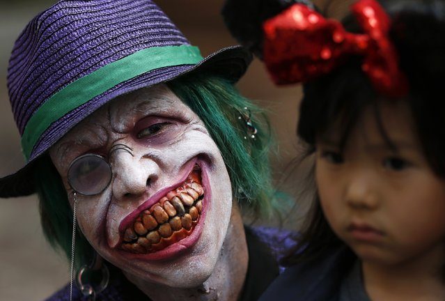 A participant in costume pose next to a girl before a Halloween parade in Kawasaki, south of Tokyo, October 26, 2014. (Photo by Yuya Shino/Reuters)
