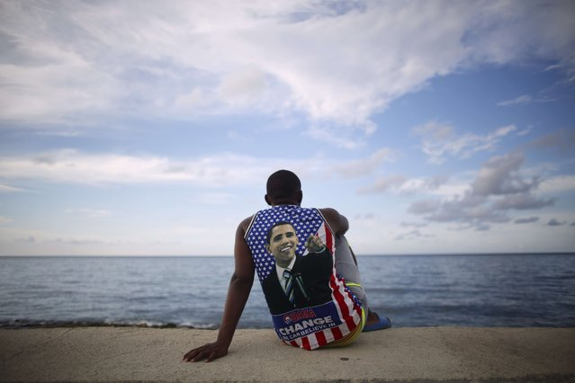 Medical student Electo Rossel, 20, wearing a shirt with a picture of U.S. President Barack Obama, listens to music at the Malecon seafront outside the U.S. embassy (not pictured) in Havana, Cuba, in this file photo taken August 14, 2015. (Photo by Alexandre Meneghini/Reuters)