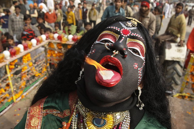 "A man dressed as Hindu goddess Kali, the goddess of power, performs with a burning camphor tablet on his tongue during a religious procession ahead of the ""Kumbh Mela"", or Pitcher Festival, in the northern Indian city of Allahabad January 6, 2013. During the festival, hundreds of thousands of Hindus take part in a religious gathering at the banks of the river Ganges. The festival is held every 12 years in different Indian cities. (Photo by Jitendra Prakash/Reuters)"