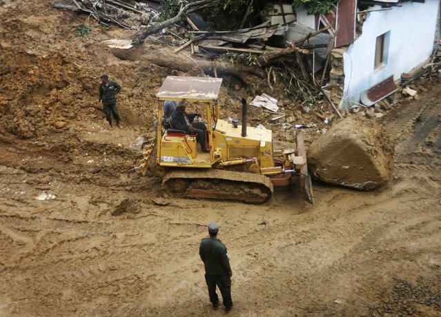 Rescue workers use a bulldozer to push a rock past a destroyed building at the site of a landslide at the Koslanda tea plantation near Haldummulla October 30, 2014. (Photo by Dinuka Liyanawatte/Reuters)