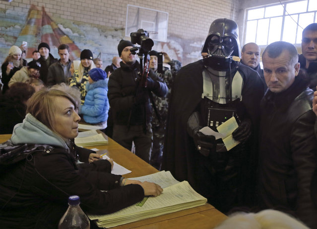 Darth Vader, previously known as Viktor Shevchenko, center, the leader of the Ukrainian Internet Party, waits to receive his ballot papers at a polling station during parliamentary elections in Kiev, Ukraine, Sunday, October 26, 2014. Voters in Ukraine headed to the polls Sunday to elect a new parliament, overhauling a legislature tainted by its association with ousted President Viktor Yanukovych. (Photo by Efrem Lukatsky/AP Photo)