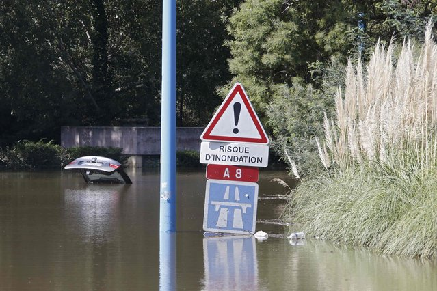 "A traffic warning sign reads, ""Danger of Flooding"" near an abandoned car that is submerged in deep water near the autoroute after flooding caused by torrential rain in Mandelieu, France, October 4, 2015. (Photo by Eric Gaillard/Reuters)"