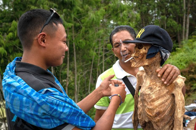 """Family members give cigarettes to the preserved body of their relative during a traditional ritual called """"Manene"""" in Panggala, Nort Toraja, South Sulawesi, Indonesia, Tuesday, August 25th 2020. (Photo by Hariandi Hafid/ZUMA Wire/Rex Features/Shutterstock)"""