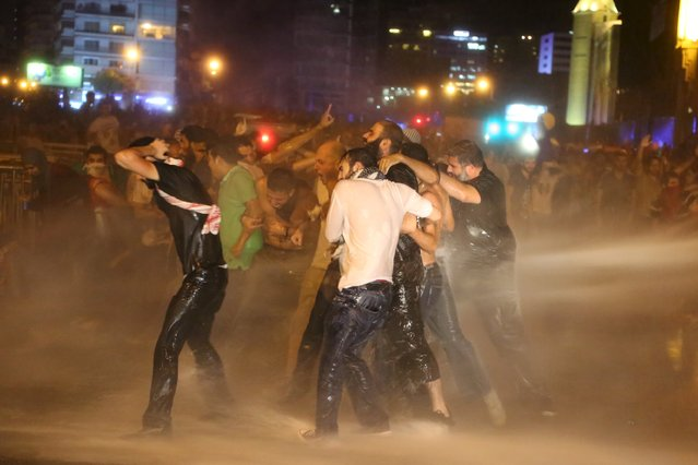Protesters hold on to each other as they are sprayed with water from police water cannons in Martyr square, downtown Beirut, Lebanon October 8, 2015. (Photo by Aziz Taher/Reuters)