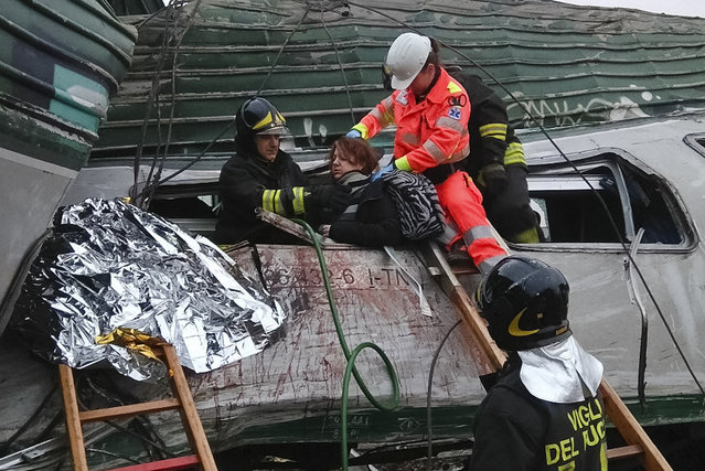 A woman is helped out of the wrecked car of a train that derailed at the station of Pioltello Limito, on the outskirts of Milan, Italy, Thursday, January 25, 2018. Italian officials said that the commuter train derailed in northern Italy, killing some people, seriously injuring 10 and trapping others heading into Milan at the start of the work day. (Photo by AP Photo/Stringer)