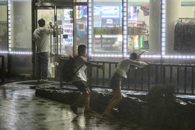 A man runs to help a woman as they attempt to shelter in a locked convenience store during heavy wind and rain as typhoon Maysak hits the Haeundae Beach area of Busan, South Korea, on September 3, 2020. Flights were grounded in South Korea and storm warnings issued on both sides of the Korean peninsula as a typhoon forecast to be one of the most powerful in years made its approach. (Photo by Ed Jones/AFP Photo)