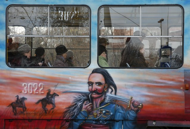 People ride a tram with a painting depicting a Ukrainian Cossack in Donetsk, November 10, 2014. (Photo by Maxim Zmeyev/Reuters)