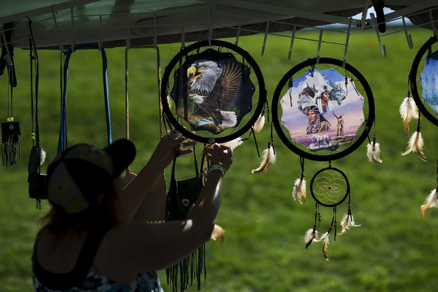 "A woman organizes indigenous items after a Sunrise Ceremony during a ""pow-wow"" celebrating the Indigenous Peoples Day Festival in Randalls Island, New York, October 12, 2015. (Photo by Eduardo Munoz/Reuters)"