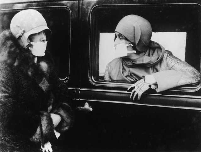 Two women wearing flu masks during the flu epidemic which followed the First World War, 1929. (Photo by Keystone/Getty Images)