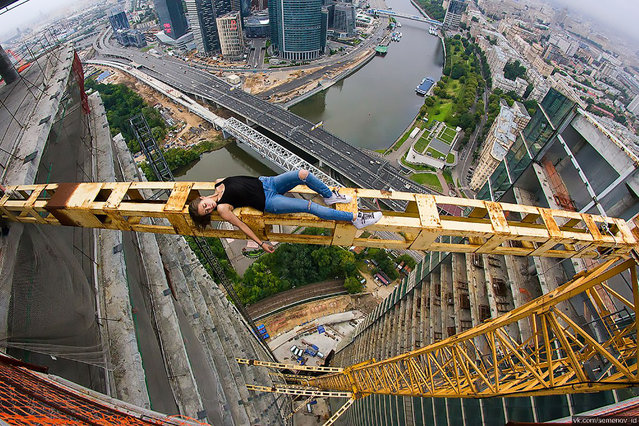 """An astonishing set of snaps of a thrill-seeker's sky-high catwalk show on the edge of some of the world's tallest buildings has turned her into a social media sensation. Daredevil Angelina Nikolau, 23, from Russia, has spent weeks travelling around China and Hong Kong posing for jaw-dropping skyscraper selfies hundreds of feet above the ground. Her vertigo inducing results – uploaded to Instagram – have made her an instant star on the internet. Angelina is described by Russian media as """"self-taught photographer, adventurer and roofer from Moscow"""". Roofing – also known as rooftopping – is where people get as close as possible to the edge of a skyscraper's highest point to take selfies. Angelina's dizzying combination of catwalk poses and looks and sheer nerve have won her an army of fans. (Photo by Kirill Oreshkin/CEN)"""