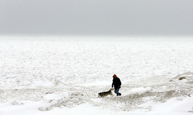 A man walks with his dog next to snow-covered Lake Michigan in Chicago, February 22, 2013. Gusty winds and iced-over roadways made for treacherous Midwest travel Friday as a major winter storm headed east over the Great Lakes. (Photo by Nam Y. Huh/Associated Press)