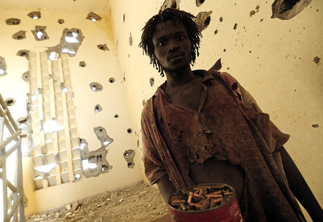 A man collects spent cartridge cases at a damaged police station one day after Islamist gunmen battled French and Malian troops, on February 11, 2013 in Gao. (Photo by Pascal Guyot/AFP Photo/The Atlantic)