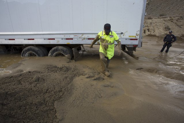 A worker walks through mud while preparing to pull a truck mired in mud and debris on State Route 58 near Tehachapi, California, about 60 miles (97 km) outside of Los Angeles October 17, 2015. (Photo by David McNew/Reuters)