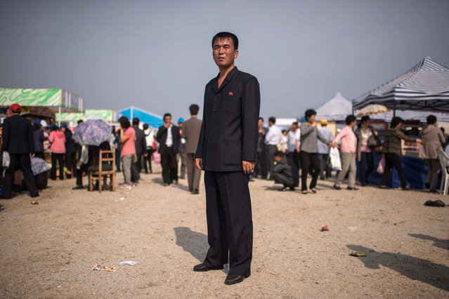 A man stands between food and gift stalls at the first Wonsan Friendship Air Festival in Wonsan on September 24, 2016. (Photo by Ed Jones/AFP Photo)