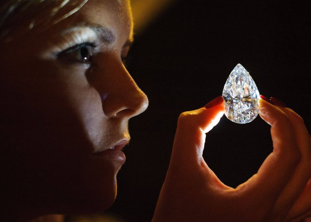 A Christie's employee (name withheld) holds a 101.73 carat pear-shaped diamond, the largest D colour flawless diamond ever to be offered for sale at auction, which is expected to fetch in excess of $20 million (£13.36 million), during a photocall at Christie's auction house, in central London, on March 13, 2013. (Photo by Dominic Lipinski/PA Wire)